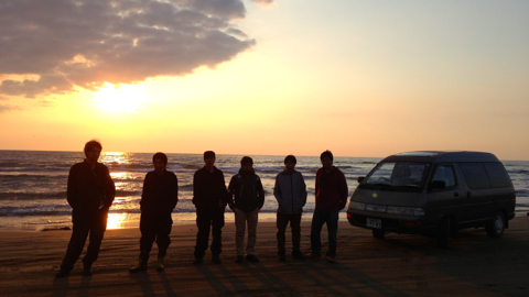 夕陽を背景に浜辺にて集合写真